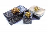 Three Gift Boxes Are Black-gold With A Geometric Pattern And A Gold Bow And Black With A White And G poster