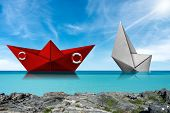 Rescue Concept. Red Paper Rescue Boat Of The Coast Guard And White Boat That Are Sinking, In A Turqu poster