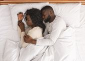 Black Married Couple Sleeping In Bed And Cuddling, Husband Tenderly Hugging Wife From Back, Top View poster