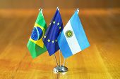 Three Flags On The Table. Flags Of Brazil, European Union And Argentina. Flags Of Brazil, European U poster