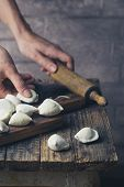 The Process Of Making Homemade Dumplings. Raw Homemade Dumplings With Meat On A Wooden Board With Wo poster