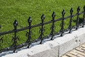 foto of old stone fence  - Iron black old decorative ornamented fence - JPG