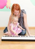 image of babysitter  - Little girl and her mother playing the piano sitting on the floor - JPG