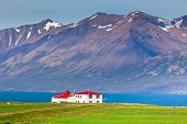 stock photo of red siding  - White Siding House with Red Roof at coastline in North Iceland - JPG