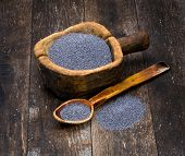 picture of doughy  - poppy seeds in a wooden bowl on a background of the old wooden table - JPG