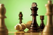 stock photo of wood pieces  - Chess a game of skill and planning with the winning dark king chess piece declaring check mate on the fallen light wood king in a concept of winning and leadership - JPG