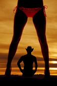 stock photo of bare butt  - A silhouette of a womans legs in a bikini with a cowboy in the back - JPG