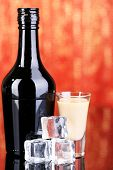 picture of bailey  - Baileys liqueur in bottle and glass on red background - JPG