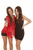 foto of two women taking cell phone  - Two women are taking a picture of themselves with a cell phone - JPG
