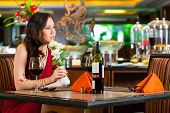 Chinese nervous, hoping, lonely, dreamy, heartsick woman in a restaurant waiting for a date got stoo