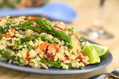 stock photo of quinoa  - Vegetarian quinoa dish with green asparagus and red bell pepper sprinkled with parsley and roasted sunflower seeds lime wedges on the side 
