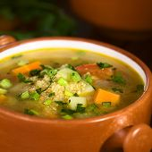 picture of scallion  - Vegetarian quinoa soup with carrot potato celery leek and tomato sprinkled with parsley and scallion 