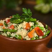 stock photo of quinoa  - Vegetarian quinoa dish with green asparagus and red bell pepper sprinkled with parsley in rustic bowl (Selective Focus Focus on the asparagus heads on the dish)