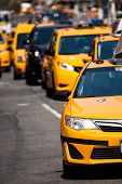 stock photo of cabs  - Yellow cab speeds through Times Square in New York NY USA - JPG