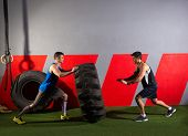 pic of tractor  - men flipping a tractor tire workout exercise at gym - JPG
