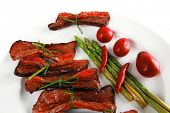grilled red beef meat rolls with asparagus and hot spices on china plate isolated over white backgro