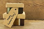 stock photo of gift wrapped  - Fathers Day gifts with tag over a wooden background - JPG
