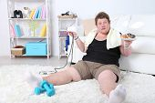 foto of unhealthy lifestyle  - Large fitness man eating unhealthy food and trying to take exercise  at home - JPG