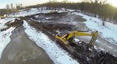 Excavators on dirt snow-covered ground reduced pond near the forest, view from unmanned quadrocopter