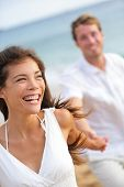 Couple on beach laughing having fun happy lifestyle. Casual young romantic woman and man running pla