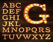 stock photo of glowing  - Vector of letters in retro style old lamp alphabet for light board on wood background - JPG
