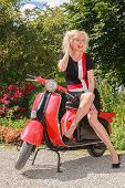 foto of vespa  - Blonde woman posing in fashionable summer dress laughing on a scooter in the park - JPG