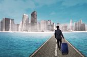 stock photo of carry-on luggage  - Business person carrying luggage and walk on the road toward modern city - JPG