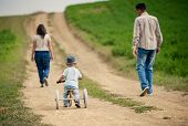 picture of tricycle  - Happy family with little boy on wooden tricycle walking in ntaure - JPG