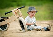 stock photo of tricycle  - Little boy with wooden tricycle in nature - JPG