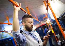 pic of tram  - Handsome hipster modern man calling by mobile phone in tram in night - JPG