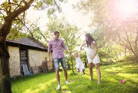 picture of farmhouse  - Happy pregnant family having fun in garden near the old farmhouse - JPG