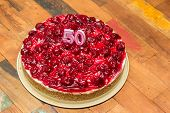 stock photo of 50th  - Cherry cheese cake with candles for 50th birthday on a wooden table