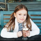 picture of hot-chocolate  - Cute little girl drinking hot chocolate in a cafe on a cold day - JPG