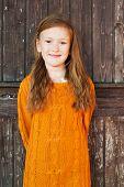 stock photo of pullovers  - Outdoor portrait of a cute little girl standing next wooden door - JPG