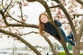 foto of magnolia  - Cute little girl playing on magnolia tree in early spring - JPG