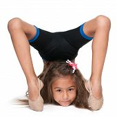 foto of gymnastic  - A smiling little gymnast does exercises against the white background - JPG