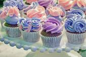 stock photo of buffet  - Delicious sweet buffet with cupcakes topped with rose - JPG
