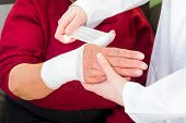 picture of bandage  - Photo of doctor bandaging the elderly woman thumb - JPG