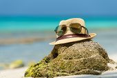 picture of beach hat  - Straw hat towel beach sun glasses and flip flops on a tropical beach - JPG