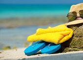 stock photo of beach hat  - Straw hat towel beach sun glasses and flip flops on a tropical beach - JPG