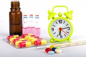stock photo of ibuprofen  - Picture of a green clock colourful pills and capsules - JPG