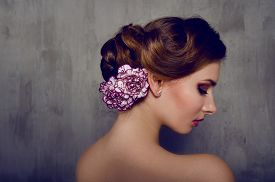 stock photo of carnation  - Beautiful woman with carnation flower in her hair with smokey eyes makeup - JPG