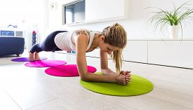 foto of stability  - Young woman doing stabilization workout in her living room - JPG