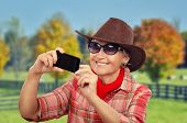 foto of cowgirl  - Aged cowgirl making selfie in front of ranch with smartphone - JPG