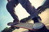pic of skateboard  - closeup of skateboarder legs riding skateboard at skatepark - JPG