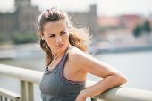 foto of jogger  - Closeup of a brunette jogger looking over her shoulder as she is resting on a bridge and looking over her shoulder while listening to music - JPG