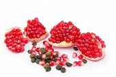 stock photo of pomegranate  - red sliced pomegranate with coffee grains and red pomegranate grains on a white background isolated - JPG