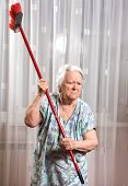 pic of broom  - Old angry woman threatening with a broom at home - JPG