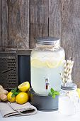 image of dispenser  - Ginger homemade lemonade in a beverage dispenser rustic lemonade stand with wooden and chalkboard background - JPG