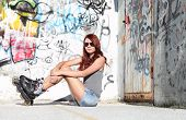 pic of roller-skating  - Sitting Girl With Roller Skates On urban wall Background - JPG